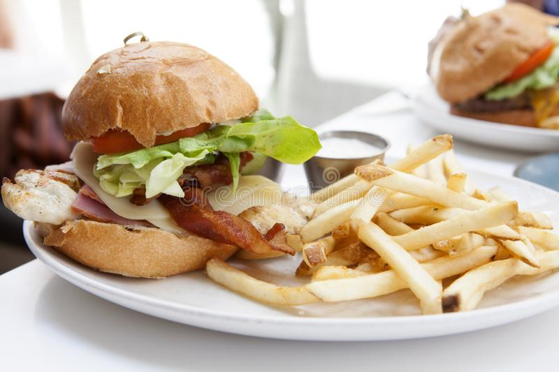 Grilled Chicken Burger with Ham and Cheese and French Fries royalty free stock photos