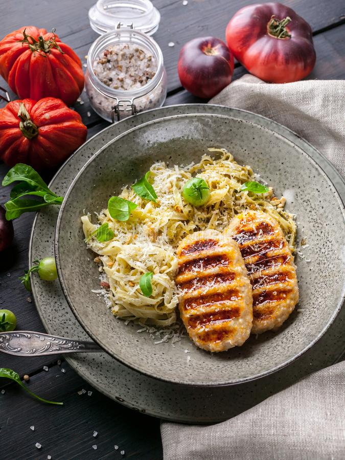 Grilled chicken burgers with spaghetti with classic pesto sauce, sweet paprika, tomatoes and fresh arugula. Vertical shot royalty free stock images