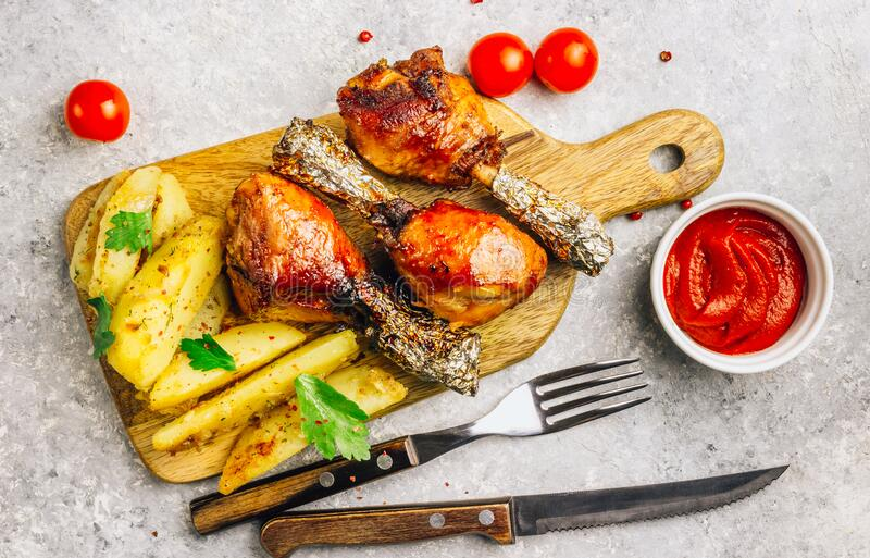 Grilled chicken drumstick bbq with potato slices on a cutting board on a stone gray background royalty free stock photo