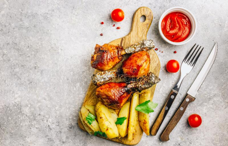 Grilled chicken drumstick bbq with potato slices on a cutting board on a stone gray background royalty free stock images
