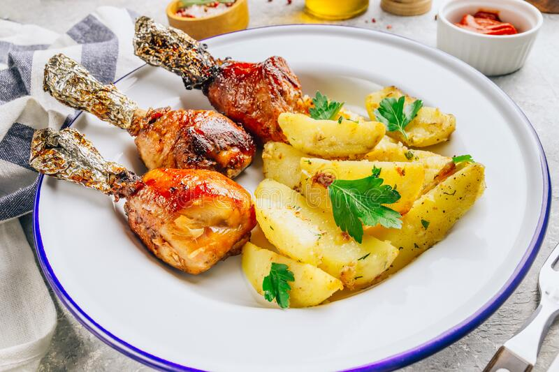 Grilled chicken drumstick bbq with potato slices on a stone gray background stock photos