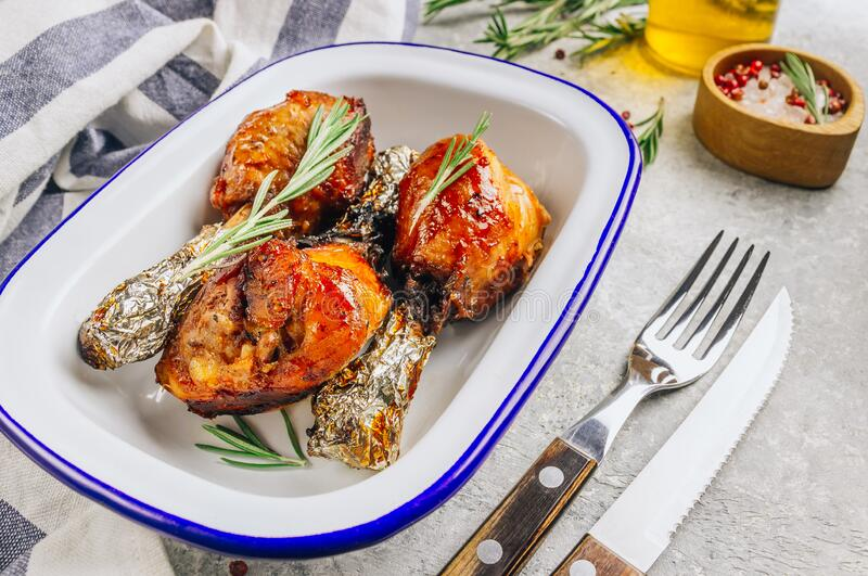 Grilled chicken drumstick bbq with rosemary on a stone gray background stock photography