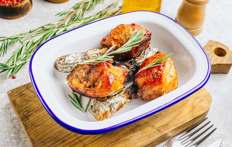 Grilled chicken drumstick bbq with rosemary on a stone gray background stock images
