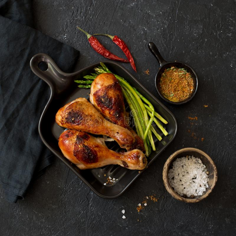 Grilled chicken drumsticks and asparagus on ceramic pan royalty free stock photos