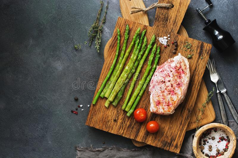 Grilled chicken fillet, asparagus, tomato and spices on a wooden cutting board, cutlery. Overhead view, copy space royalty free stock photography