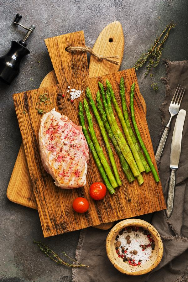 Grilled chicken fillet, asparagus, tomato and spices on a wooden cutting board, cutlery. Top view, flat lay royalty free stock images