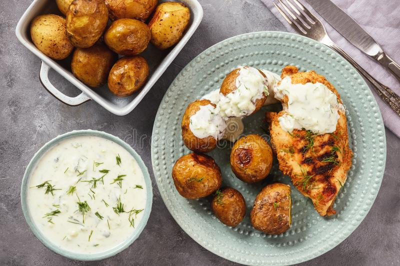 Grilled chicken fillet with baked potatoes and garlic yogurt dip. Grilled chicken fillet with baked potatoes and garlic yogurt dip royalty free stock images