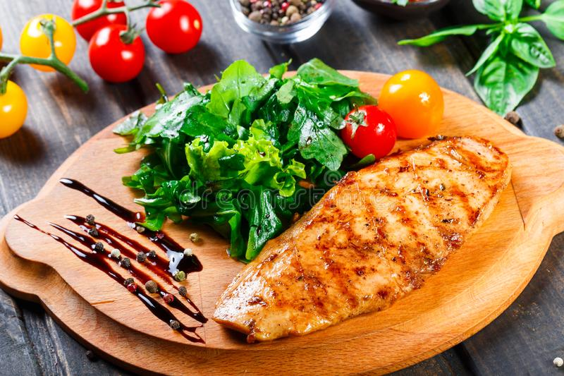 Grilled chicken fillet with fresh vegetable salad, tomatoes and sauce on wooden cutting board. Hot Meat Dishes. Top view royalty free stock photos