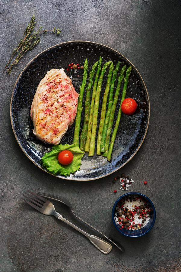 Grilled chicken fillet in a plate with asparagus, tomato and spices on a dark background. Overhead view,flat lay stock photos