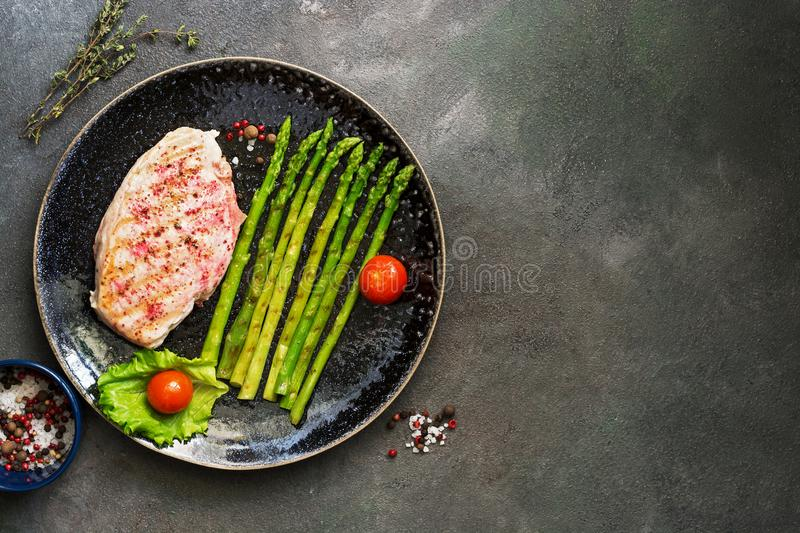 Grilled chicken fillet in a plate with asparagus, tomato and spices on a dark background. Top view, copy space royalty free stock images