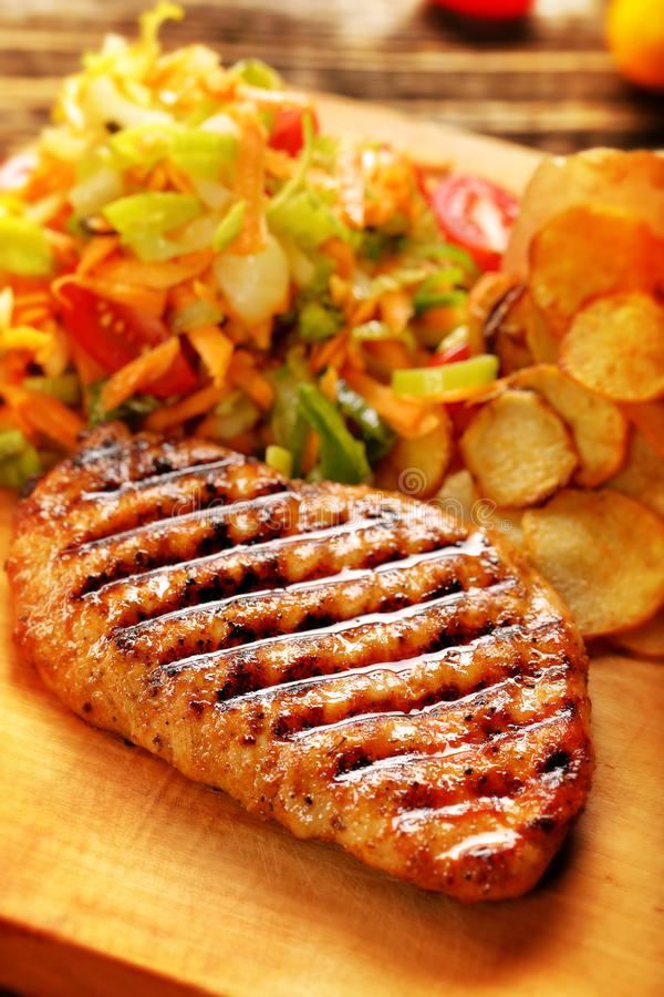 Grilled chicken fillet with potato chips and fresh salad on a wooden background royalty free stock photos