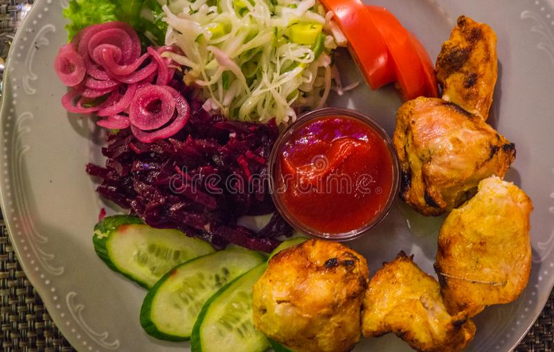 Grilled chicken fillet skewers on a plate, along with vegetables.  stock image