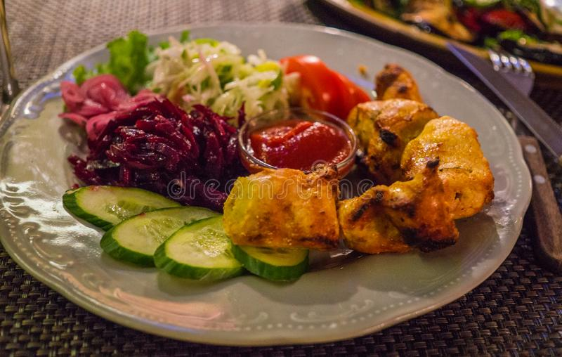 Grilled chicken fillet skewers on a plate, along with vegetables.  royalty free stock photography
