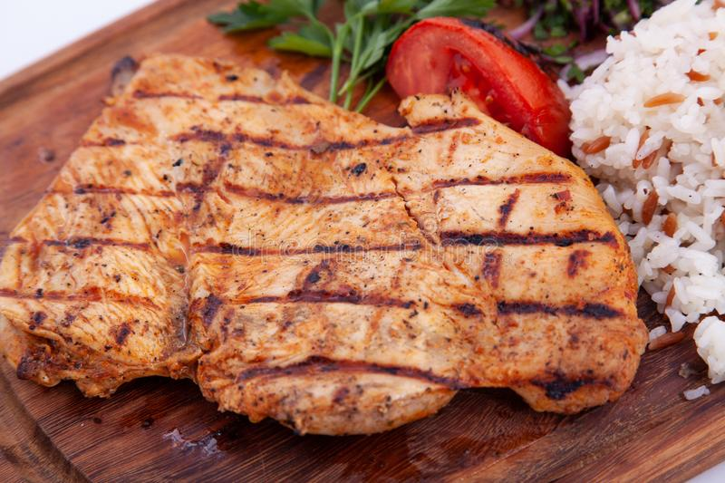Grilled chicken fillet, steak on wooden board. Close up royalty free stock photos