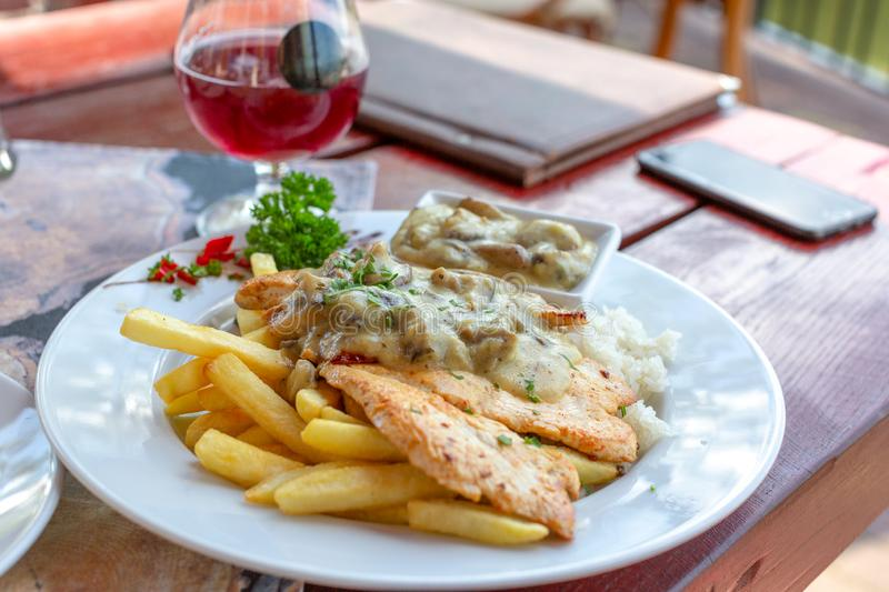 Grilled chicken fillet in white mushroom sauce with french fries on white plate. Glass of red wine in background. Grilled chicken fillet in white mushroom sauce stock photos