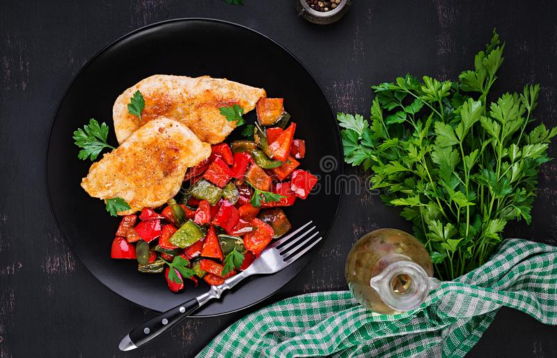 Grilled chicken fillets and sweet pepper on black plate. Top view, copy space stock photography