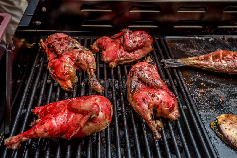 Grilled chicken and fish at street bbq. Street food barbecue with grilled chicken and fish stock photo
