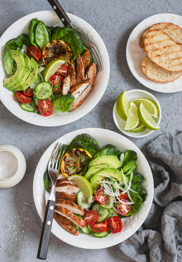 Grilled chicken and fresh vegetable salad. Healthy diet food concept. On a light background. Top view royalty free stock photo