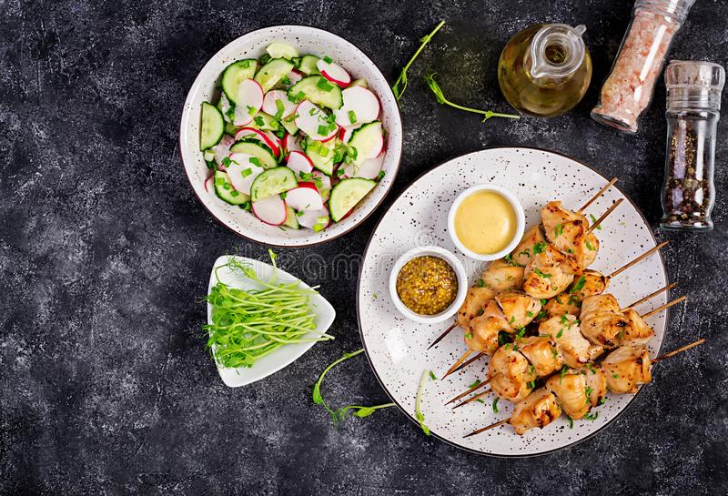 Grilled chicken kebab and salad with cucumber, radish, onion. On a dark background. Copy space. Top view stock photo