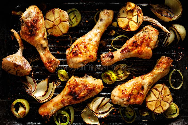 Grilled chicken legs with aromatic herbs and vegetables on a barbecue plate royalty free stock images
