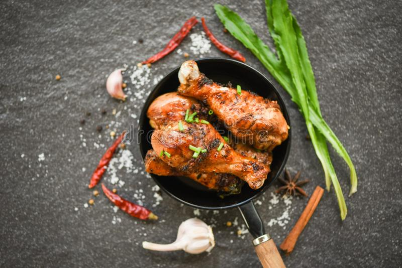 Grilled chicken legs barbecue with herbs and spices - Tasty roasted chicken legs on the pan with ingredients cooking food stock images