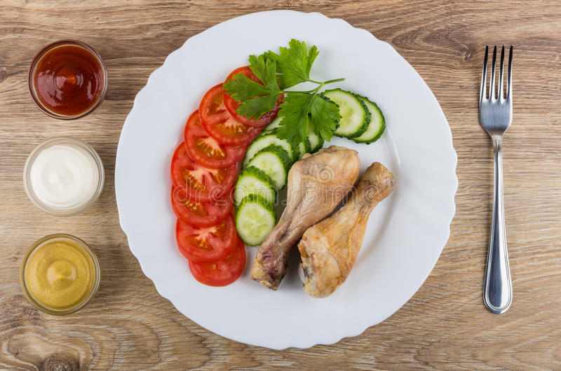 Grilled chicken legs with tomatoes and cucumbers in dish. Bowls with sauces and fork on wooden table. Top view stock photography