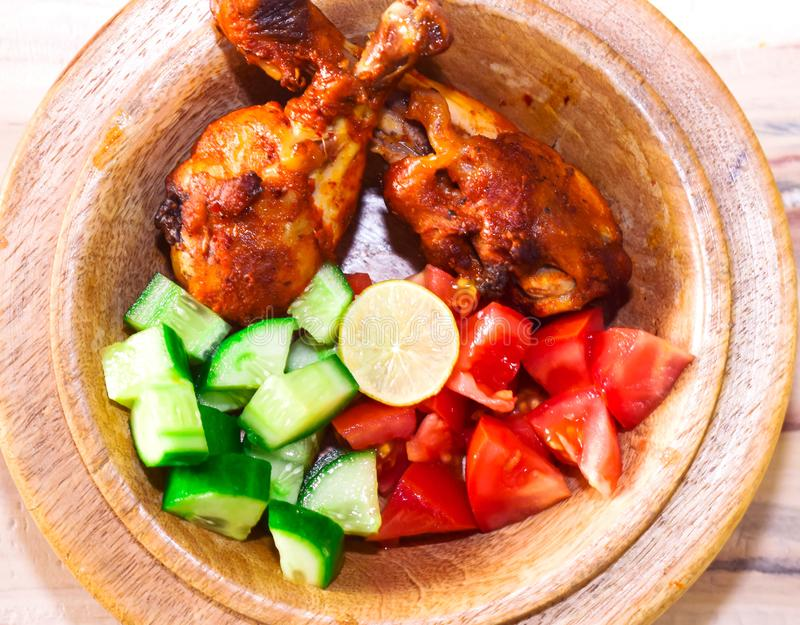 GRILLED CHICKEN WITH LEMON ,TOMATOES AND CUCUMBER royalty free stock images