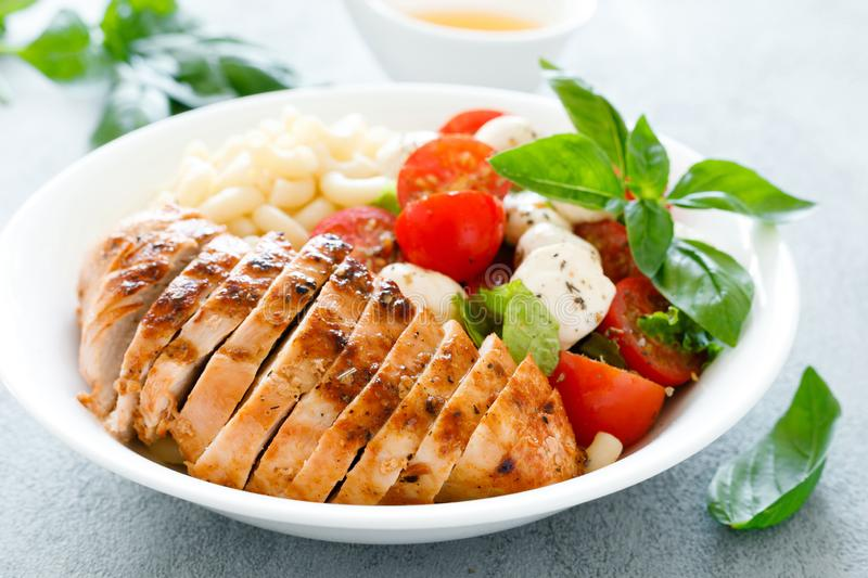 Grilled chicken lunch bowl with orange juice dressing, pasta and caprese salad royalty free stock photo