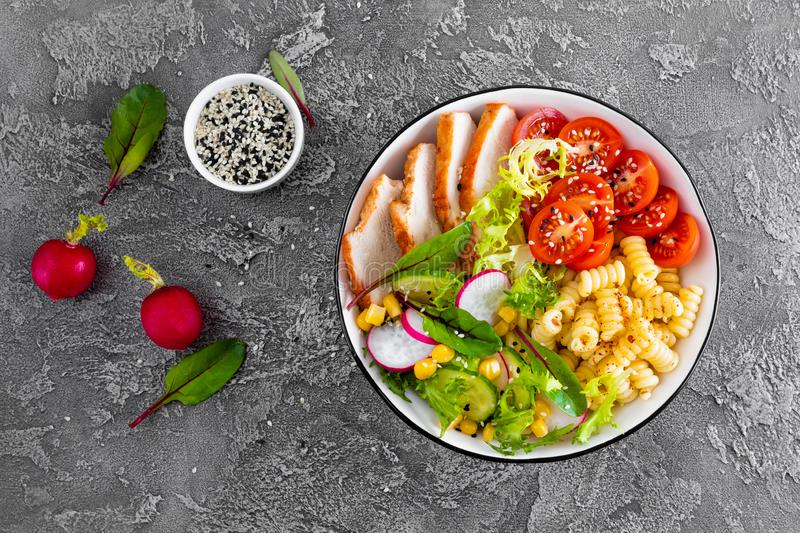 Grilled chicken meat with fresh vegetable salad of tomato, cucumber, radish, lettuce, chard leaves, corn and pasta. Healthy lunch royalty free stock images
