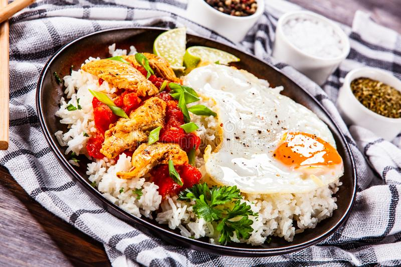 Grilled chicken meat with rice and fried egg. On wooden table royalty free stock photo