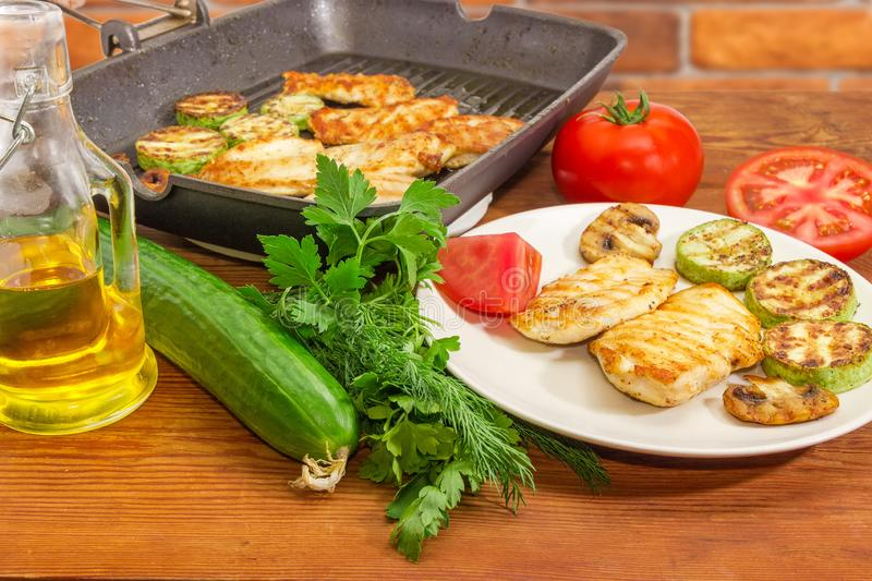 Grilled chicken meat on dish and grill pan, vegetables, greens. Grilled chicken meat, vegetables and mushrooms on the white dish and grill pan, separately raw royalty free stock image