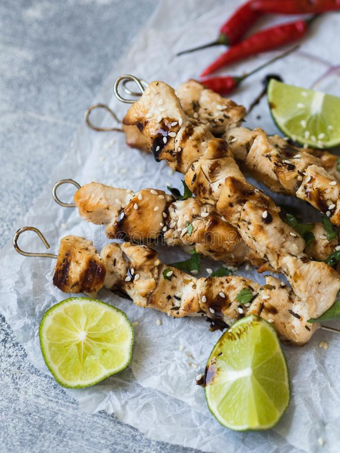 Grilled chicken on metal skewers on paper, lime and chili on grey background royalty free stock photos