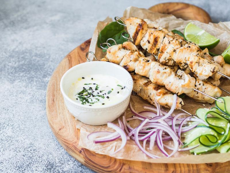 Grilled chicken on metal skewers on spinach leaves, slices cucumber, red onion and lime and sauce in a bowl on wood board royalty free stock photo