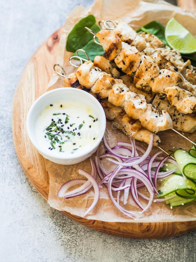 Grilled chicken on metal skewers on spinach leaves, slices cucumber, red onion and lime and sauce in a bowl on wood board royalty free stock photography