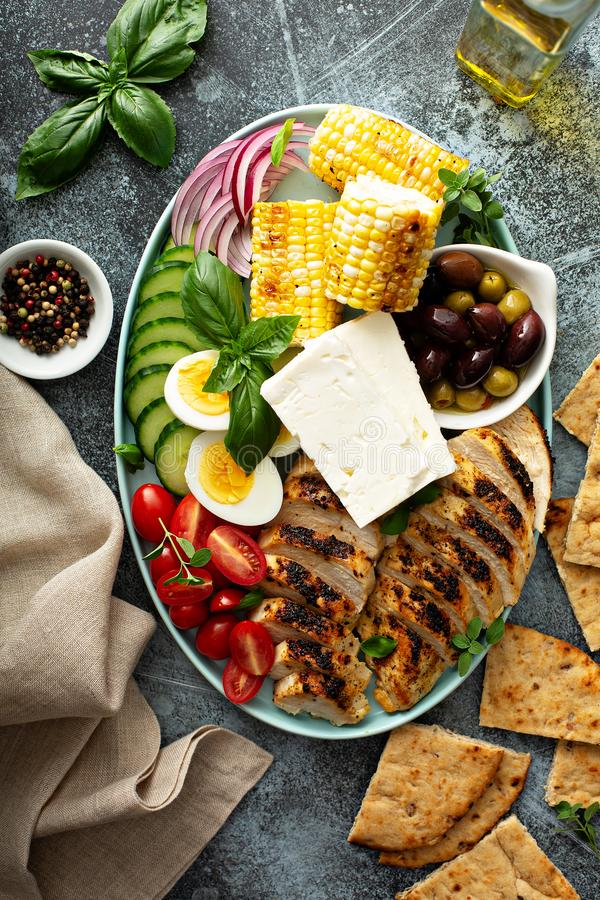 Grilled chicken platter with vegetables, eggs, feta cheese royalty free stock photos