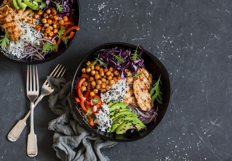 Grilled chicken, rice, spicy chickpeas, avocado, cabbage, pepper buddha bowl on dark background, top view. stock image