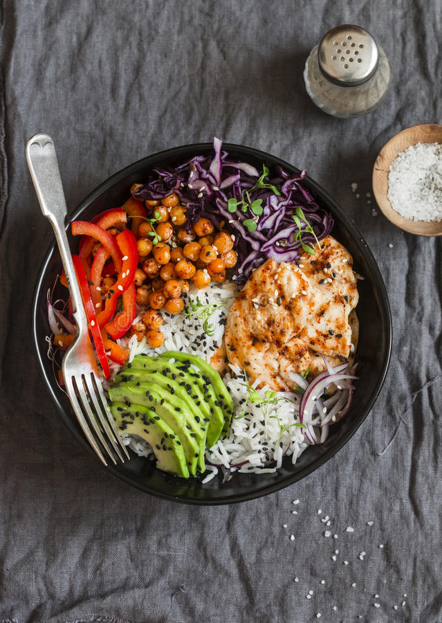 Grilled chicken, rice, spicy chickpeas, avocado mash, cabbage, pepper buddha bowl on dark background, top view. stock image