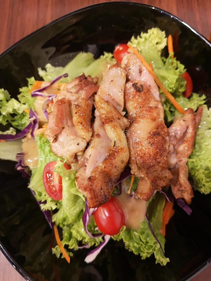 Grilled chicken salad with green leaves and tomatoes 免版税库存照片