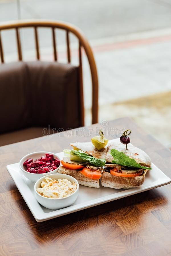 Grilled chicken sandwich made with homemade bread, tomato and lettuce served with beetroot salad and coleslaw stock image
