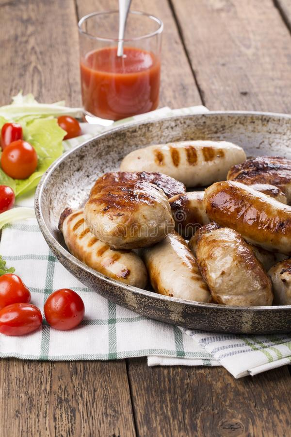 Grilled chicken sausages and burgers stock photo