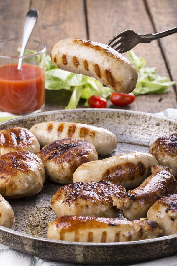 Grilled chicken sausages and burgers royalty free stock photo
