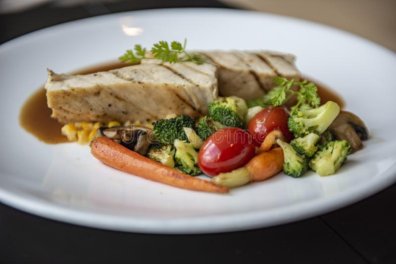 A grilled chicken served with broccoli, red tomato, carrot, mushroom and corn in Asian style. Served as a main course in a modern French restaurant in Bangkok stock photo