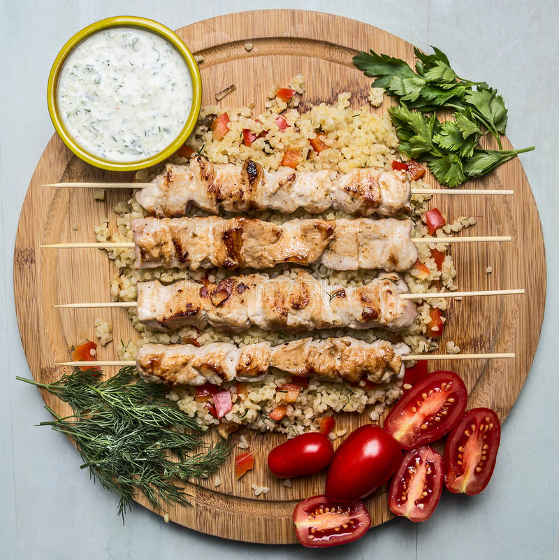Grilled chicken on skewers with garlic sauce and bulgur dill parsley and tomatoes on a cutting board wooden background top view stock images