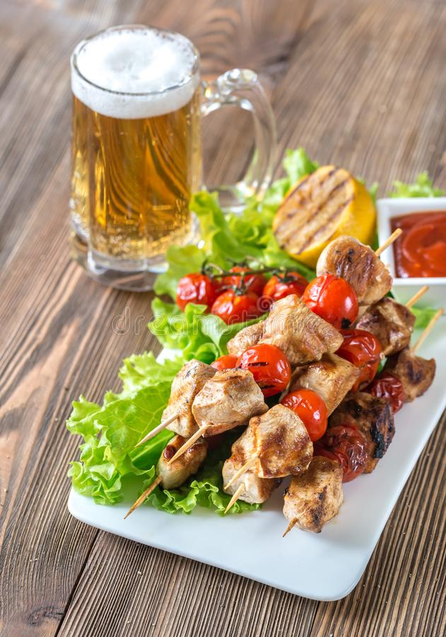 Grilled chicken skewers with mug of beer stock image
