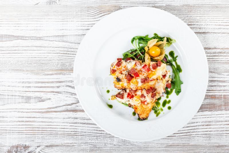 Grilled chicken steaks with cheese, vegetables, ham and salad from arugula, physalis on wooden background stock image