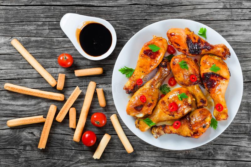 Grilled chicken sticky drumsticks marinated with honey and ginger, top-view stock images