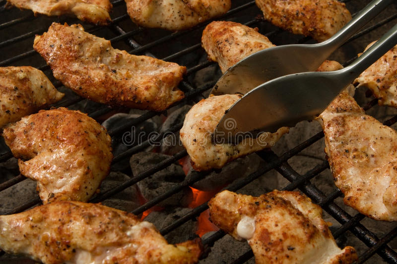 Grilled Chicken Tenders on a Charcoal Grill. Spicy chicken tenders being grilled over a medium heat charcoal grill. The focus is on the one in the center about stock image
