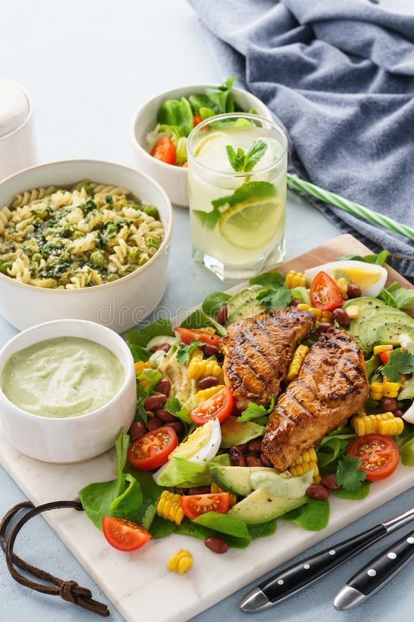 Grilled chicken with vegetable salad, soup and cold lemonade. Grilled chicken breast with fresh vegetable salad, soup and cold lemonade with mint. Healthy royalty free stock photography