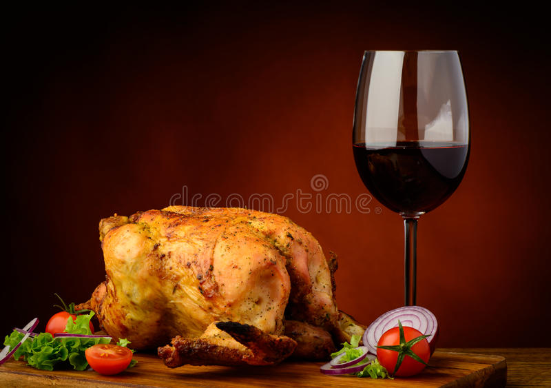 Grilled chicken and wine. Still life with grilled chicken and glass of red wine royalty free stock photography