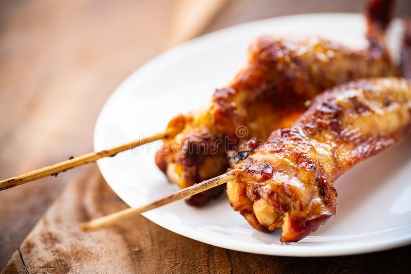 Grilled chicken wing with bamboo stick. Close up of grilled chicken wing with bamboo stick, Thai style stock image